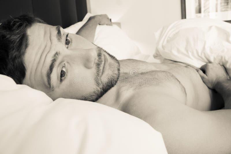 Без рубашки сексуальный первоклассный человек с бородой лежит нагой в кровати стоковое изображение
