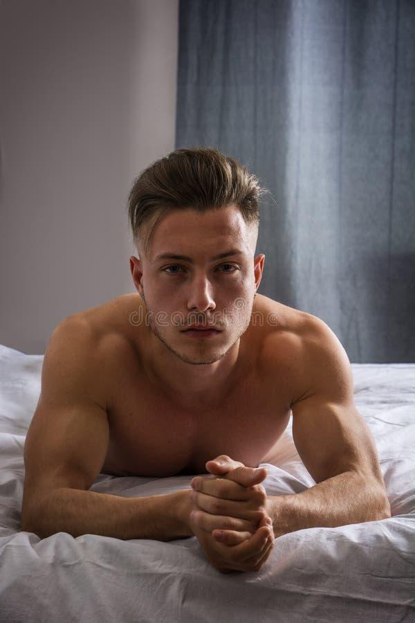 Без рубашки сексуальная мужская модель лежа самостоятельно на его кровати стоковая фотография rf