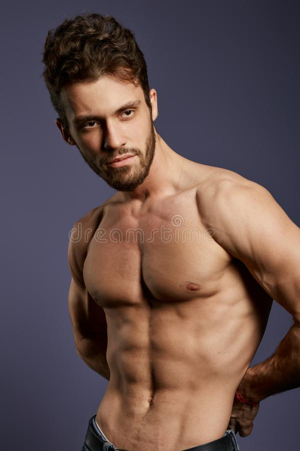 Без рубашки сильное крепкое положение парня в студии с черной стеной стоковые изображения rf