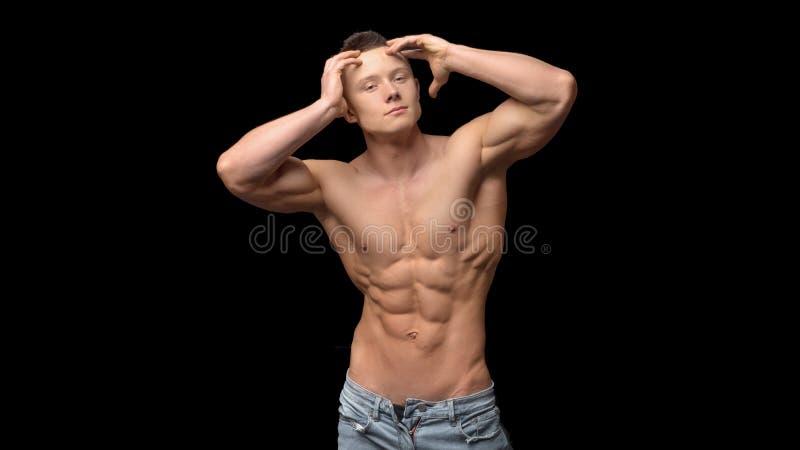 Без рубашки, фитнес сформировал мышечных людей с идеальным sporty телом только в джинсах с оружиями поднятыми к голове представля стоковое фото rf