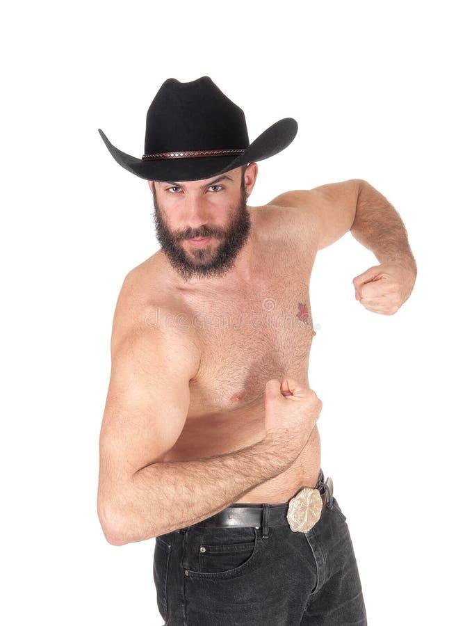 Без рубашки человек при ковбойская шляпа показывая его мышцы стоковое фото