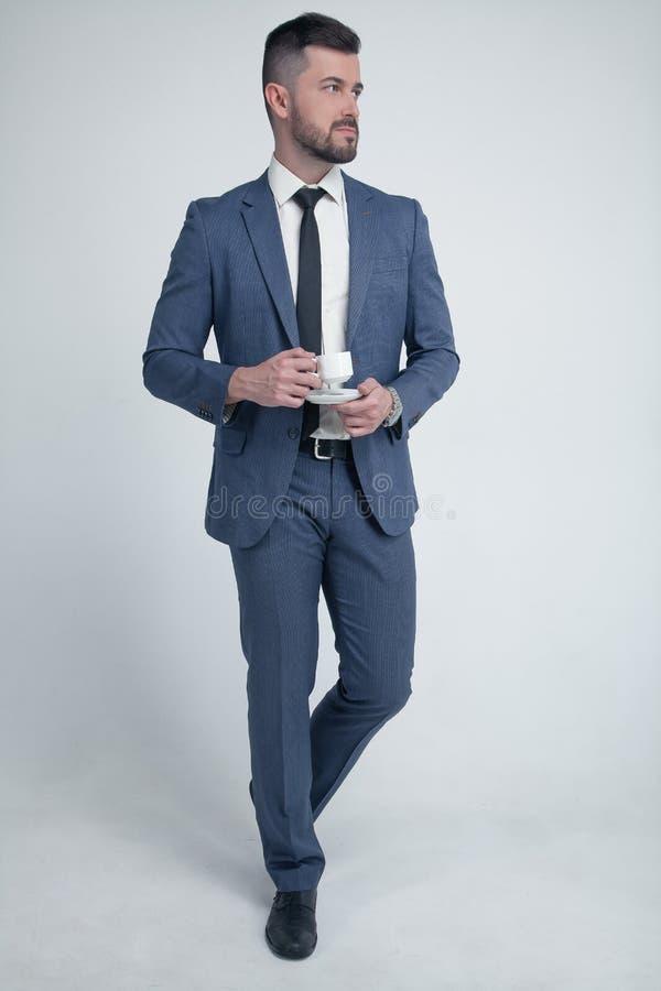 Без сокращений бизнесмен портрета a со стильными hairdo и бородой держит чашку кофе и смотрит серьезно на партии стоковые изображения rf