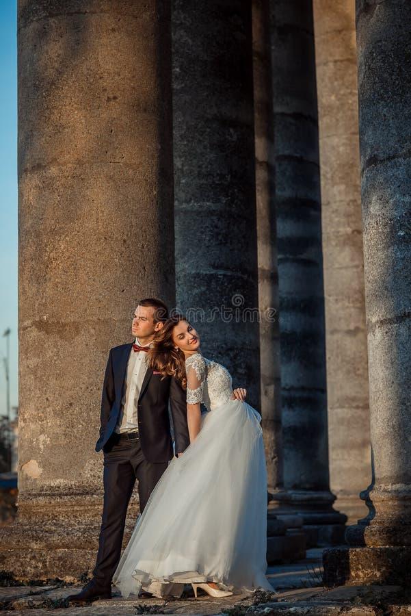 Без сокращений вертикальная свадьба сняла стильных привлекательных пар новобрачных представляя среди старых colomns Невеста стоковая фотография