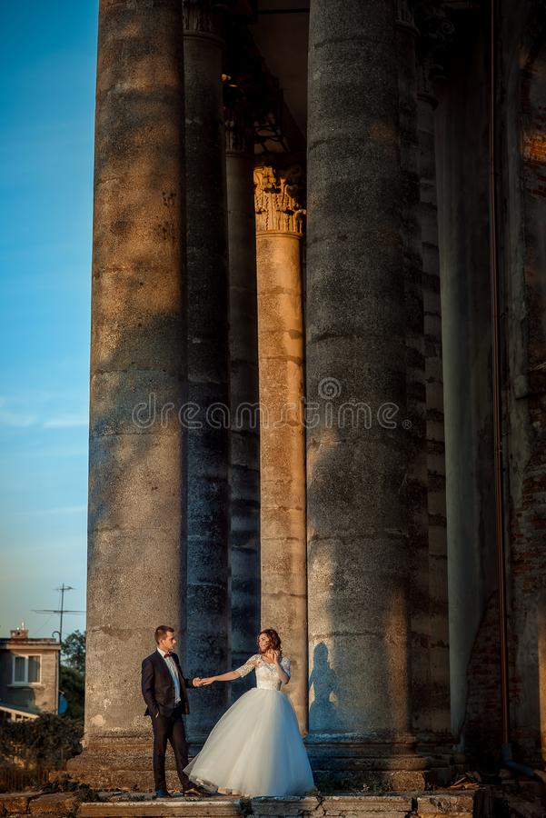 Без сокращений вертикальная съемка Очаровательная пара новобрачных нежно держит руки около старого catsle во время захода солнца стоковые фотографии rf