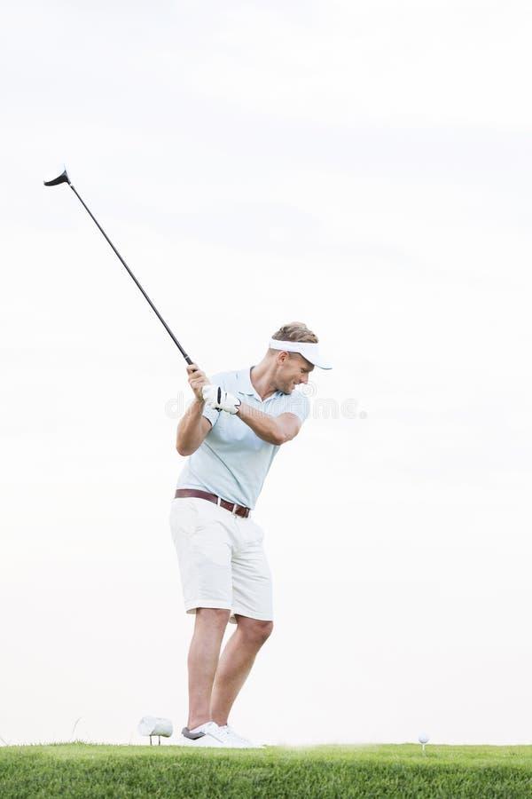 Без сокращений гольф-клуба человека средний-взрослого отбрасывая против ясного неба стоковые изображения rf