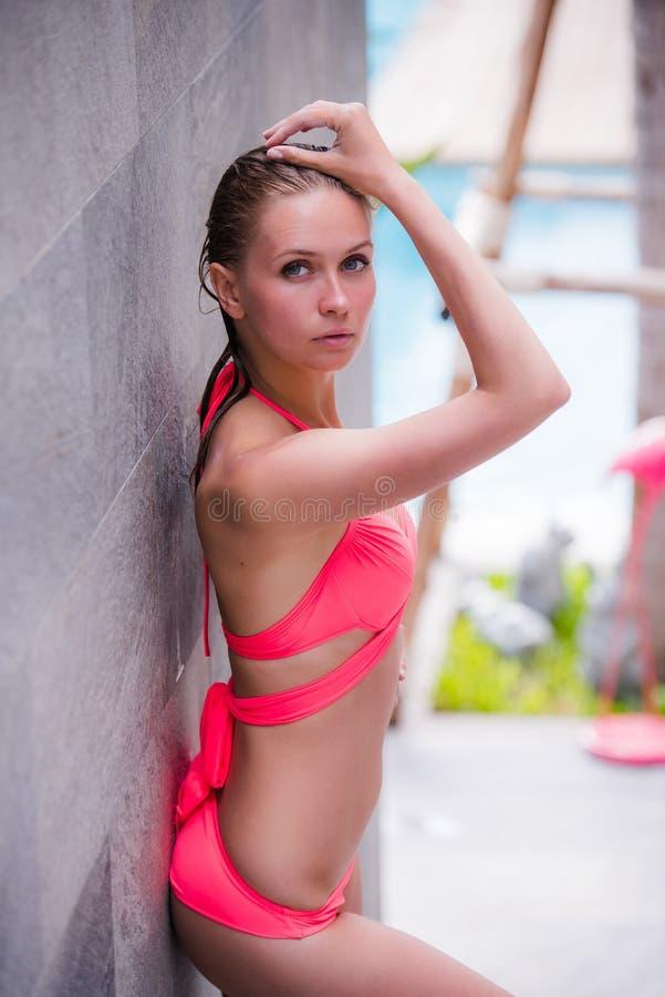 Без сокращений портрет красивой девушки в розовом купальнике с shapely телом представляет около бассейна дальше стоковые изображения
