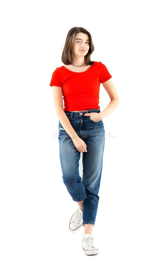 Без сокращений портрет красивой маленькой девочки нося красную футболку и джинсы полагаясь на стене на белой предпосылке, всходе  стоковое фото
