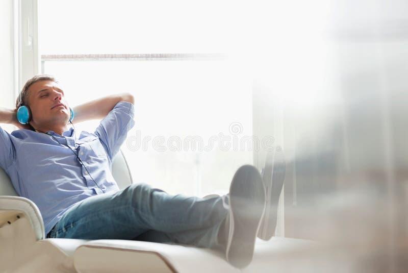 Без сокращений расслабленного Средн-постаретого человека слушая к музыке дома стоковые изображения rf