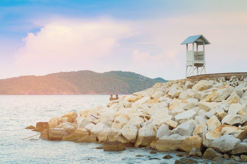 Белая безопасная стойка предохранителя над горизонтом берега моря стоковые фото