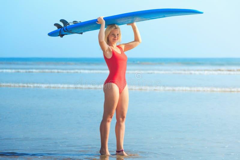 Белая белокурая девушка серфера в красном купальнике держа голубой surfboard на голове стоковое изображение rf