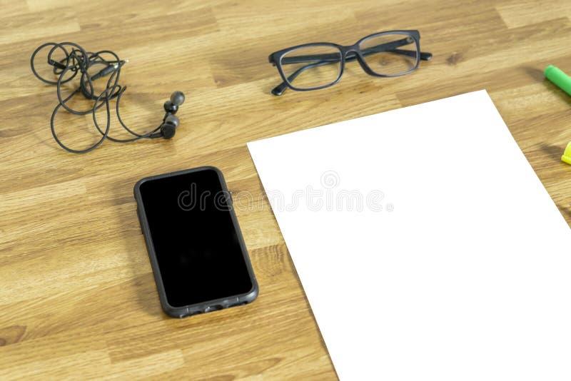 Белая бумага с наушником, мобильным телефоном, стеклами и высоко светлой стоковые фото
