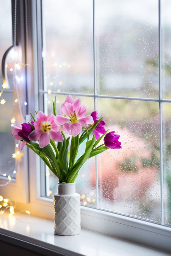 Белая ваза с нежным букетом красивых розовых тюльпанов приближает к окну с дождевыми каплями в дневном свете стоковое фото rf