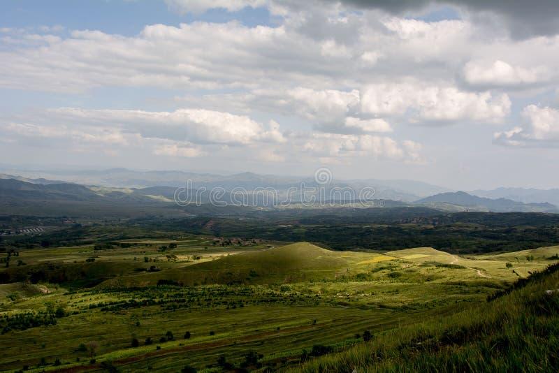 Белая ветрянка, голубое небо, белые облака, зеленые горы и воды стоковые изображения