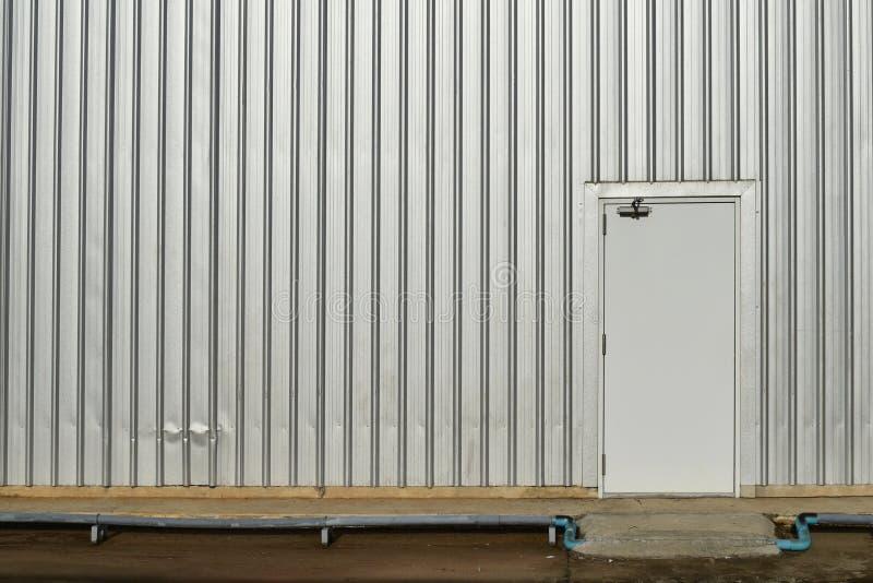 Белая дверь в старой и пакостной стене металла на пакостном бетоне стоковое изображение