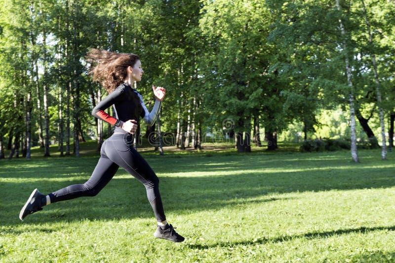 1 белая девушка с длинными волосами в одеждах спорт бежать на траве в парке стоковое изображение rf
