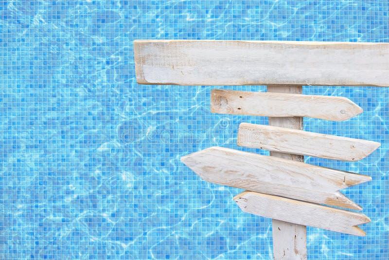 Белая деревенская деревянная стрелка подписывает сверх поверхность воды бассейна мозаики сини бирюзы стоковое фото