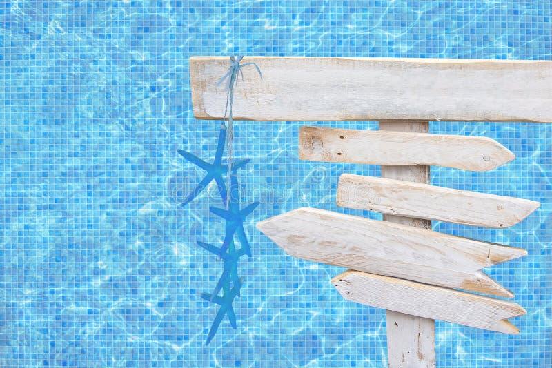 Белая деревенская деревянная стрелка подписывает с голубыми морскими звёздами над водой бассейна мозаики сини бирюзы стоковые фотографии rf