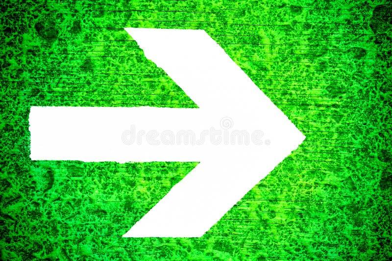 Белая дирекционная стрелка указывая к праву покрашенному на яркой ой-зелен grungy скачками деревянной текстуре стоковые изображения