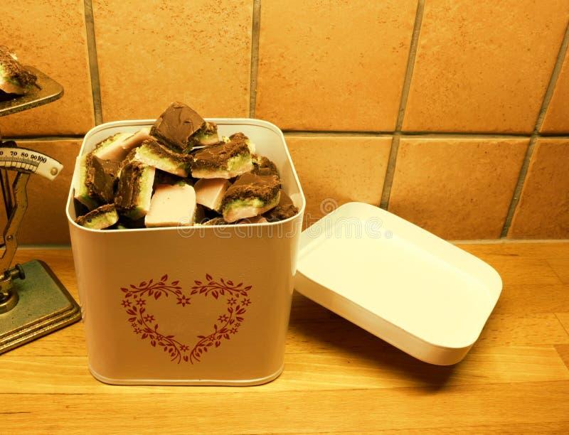 Белая жестяная коробка заполненная с домодельной красочной наслоенной кондитерскаей стоковые изображения rf