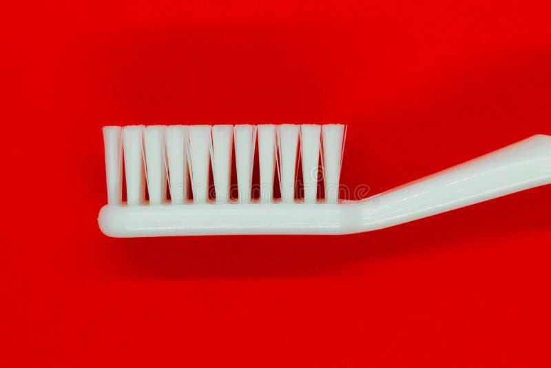 Белая зубная щетка на красной предпосылке стоковое фото rf