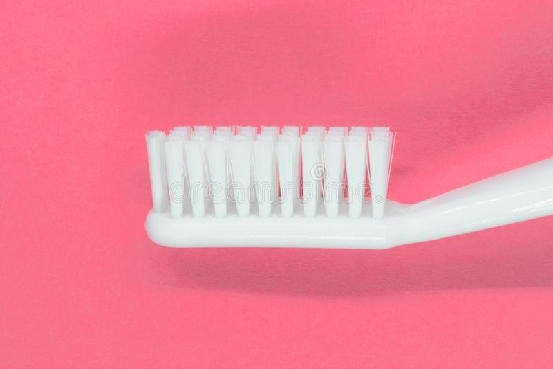 Белая зубная щетка на розовой предпосылке стоковые фотографии rf