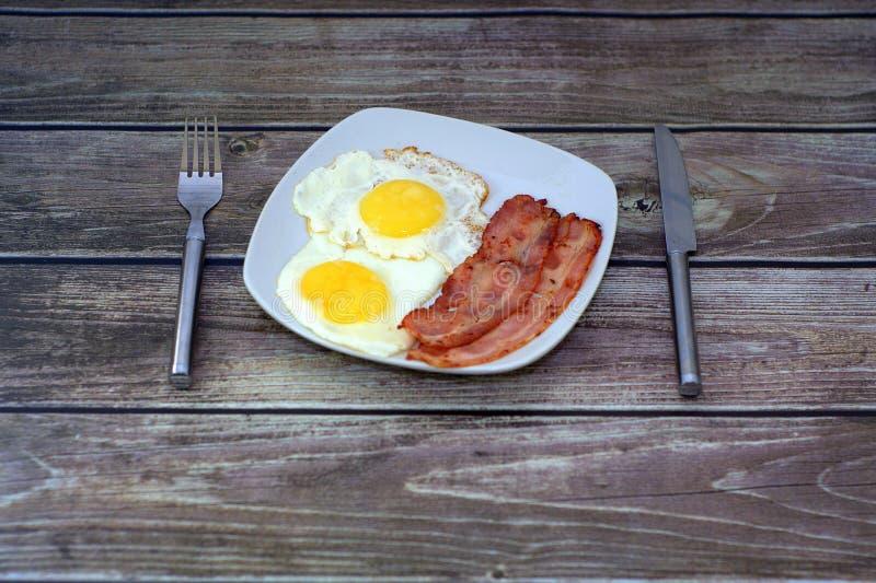 Белая квадратная плита с 2 кусками бекона и яичниц на таблице, рядом с ножом и вилкой : стоковая фотография rf