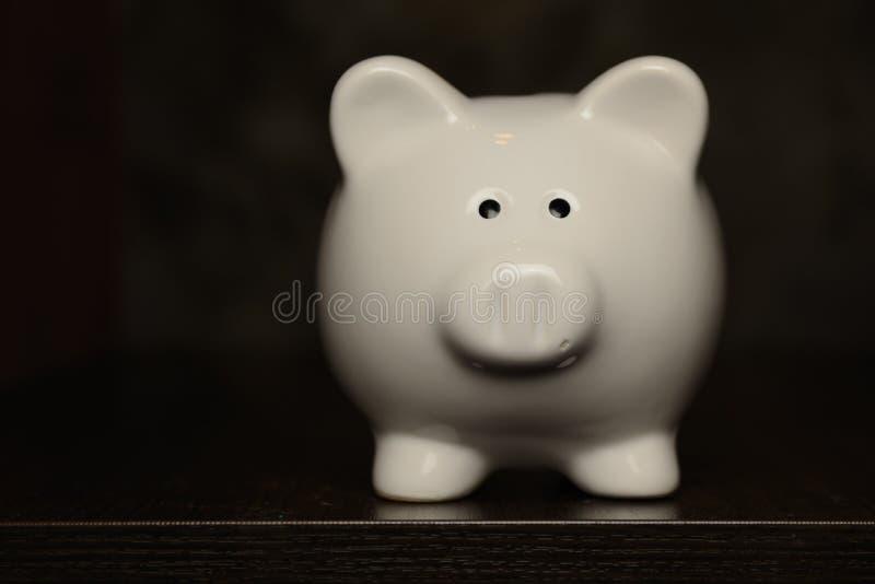 Белая керамическая копилка на деревянном столе стоковая фотография