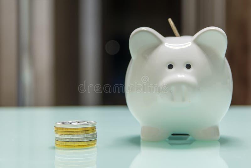 Белая керамическая копилка с кучей монеток на стеклянном столе стоковая фотография