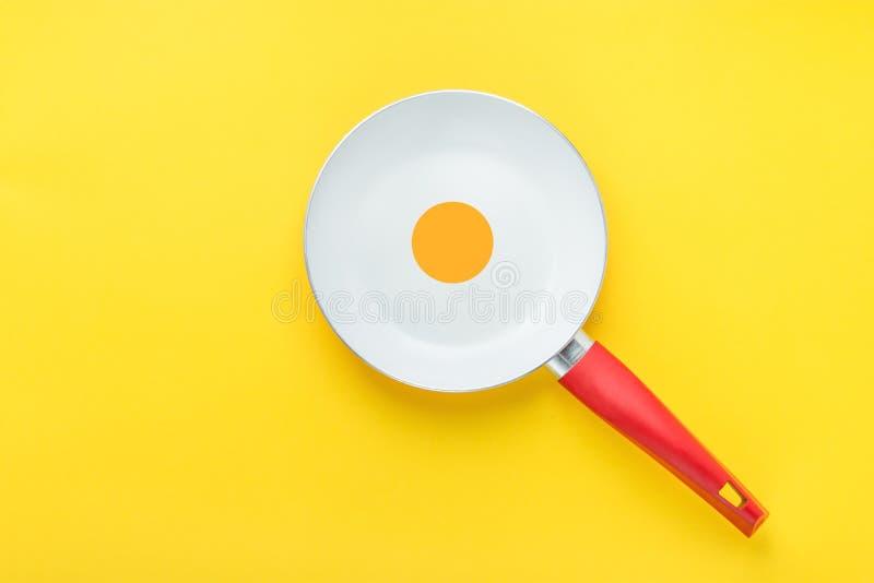 Белая керамическая сковорода с красной ручкой на яркой желтой предпосылке Желток в середине Солнечная сторона вверх по коллажу яи стоковое изображение
