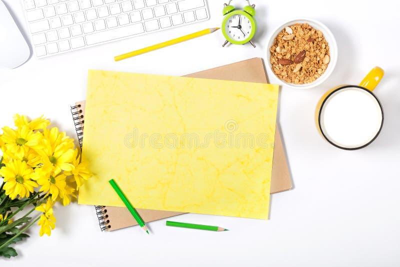 Белая клавиатура, мышь, красочные канцелярские принадлежности, желтые цветки, плита с granola и большая чашка молока на белой пре стоковое изображение