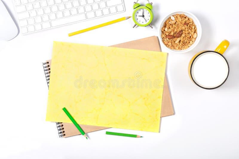 Белая клавиатура, мышь, красочные канцелярские принадлежности, часы, плита с granola и большая чашка молока на белой предпосылке стоковые изображения