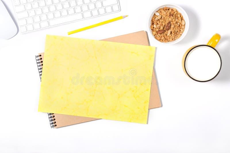 Белая клавиатура, мышь, sketchbook, желтые бумага и карандаш ремесла, плита с granola и большая чашка молока на белой предпосылке стоковые изображения rf