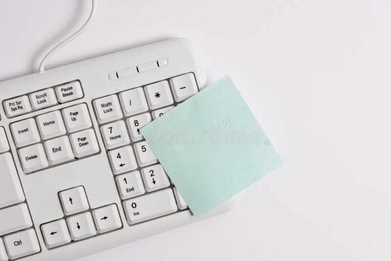 Белая клавиатура ПК с пустой бумагой примечания над белой предпосылкой Концепция дела с примечаниями и клавиатурой ПК Чистый лист стоковые изображения rf