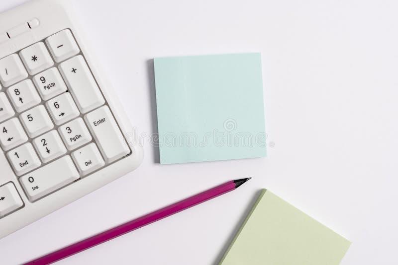 Белая клавиатура ПК с пустыми бумагой и карандашем примечания над белой предпосылкой Концепция дела с примечаниями и клавиатурой  стоковые фотографии rf