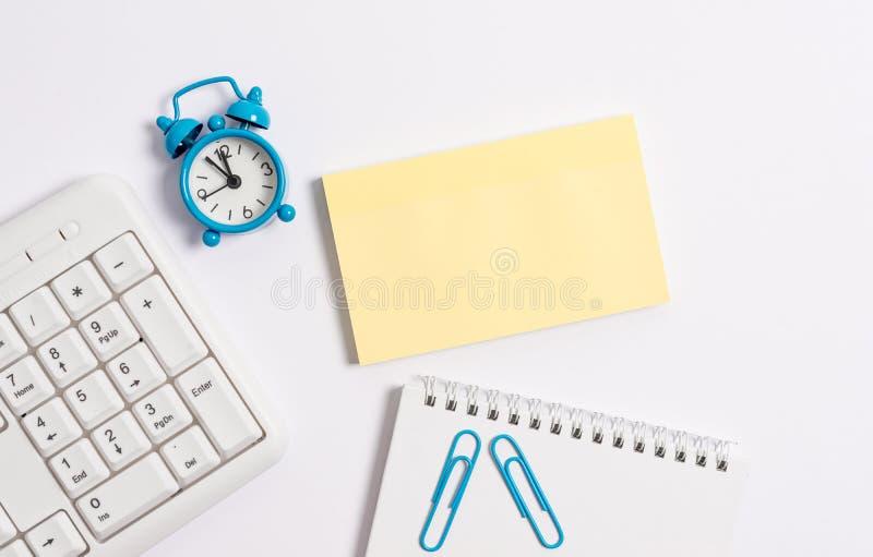 Белая клавиатура ПК с пустыми бумагой и часами примечания над белой предпосылкой Концепция дела с примечаниями и клавиатурой ПК стоковое фото