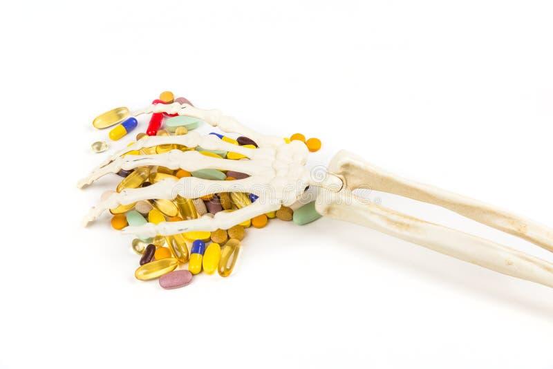 Белая костлявая каркасная ладонь руки вниз с хватать пригорошню таблеток стоковое фото