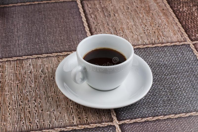 Белая кофейная чашка на таблице E стоковое фото rf