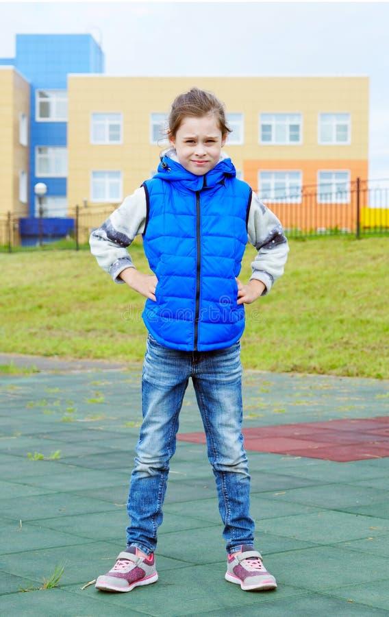 Белая красивая маленькая девочка нося голубую безрукавную куртку и голубые джинсы стоит outdoors стоковые изображения rf