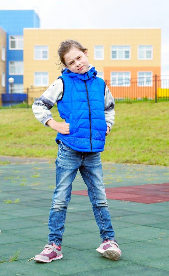 Белая красивая маленькая девочка нося голубую безрукавную куртку и голубые джинсы стоковые изображения rf