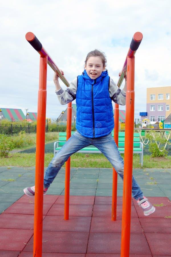 Белая маленькая девочка делая тренировки на гимнастических барах на земле спорт стоковое изображение rf