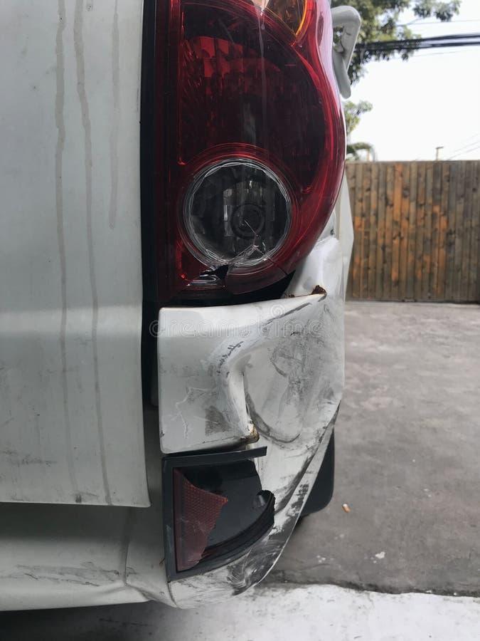 Белая машина повреждена в результате аварии на дороге В результате дорожно-транспортного происшествия поврежден пробел бампера тр стоковая фотография