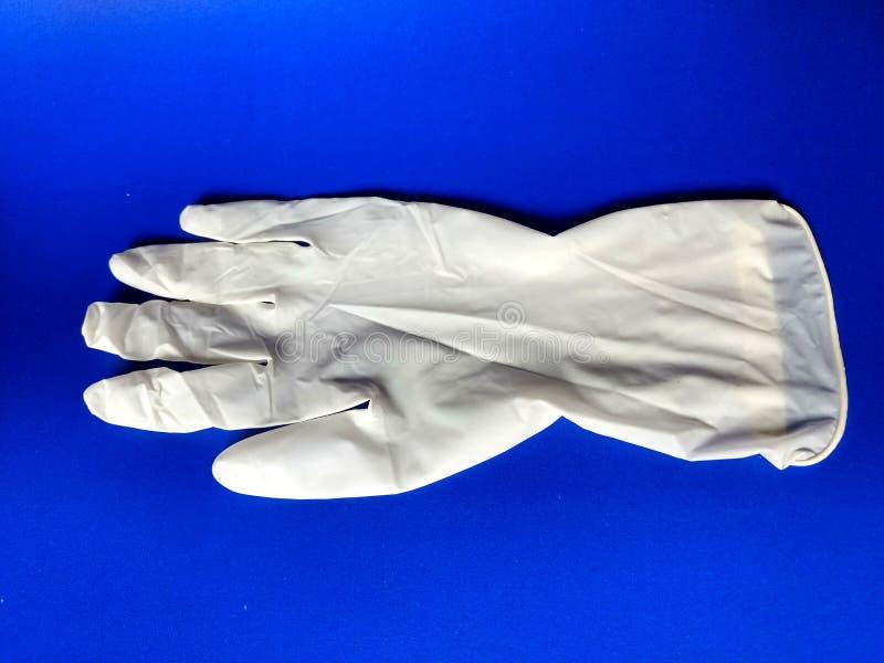 Белая перчатка латекса с голубой предпосылкой стоковое фото rf