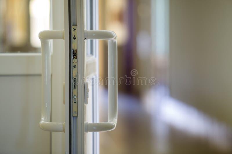 Белая пластиковая деталь двери с замком металла, ручкой и прозрачным стеклом на запачканной внутренней предпосылке Установка и ди стоковые фото