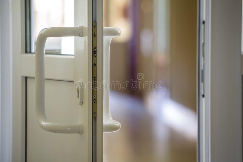 Белая пластиковая деталь двери с замком металла, ручкой и прозрачным стеклом на запачканной внутренней предпосылке Установка и ди стоковая фотография