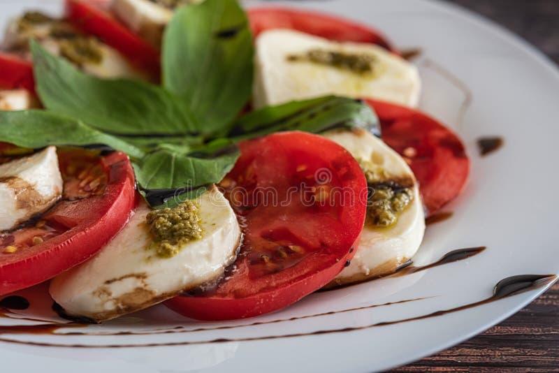 Белая плита здорового классического очень вкусного caprese салата с томатами и сыром моццареллы с листьями базилика и прокладками стоковое фото