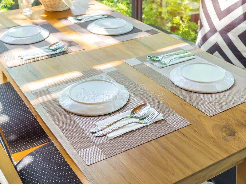 Белая плита с ложкой и вилка на циновке плиты на деревянном столе стоковая фотография rf