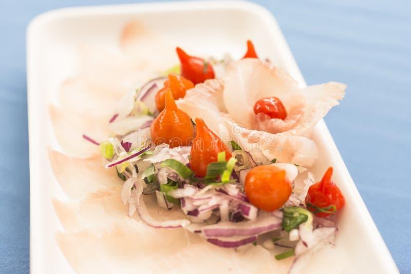 Белая плита с сасими белых рыб, пурпурным луком, красным перцем и chives стоковое фото