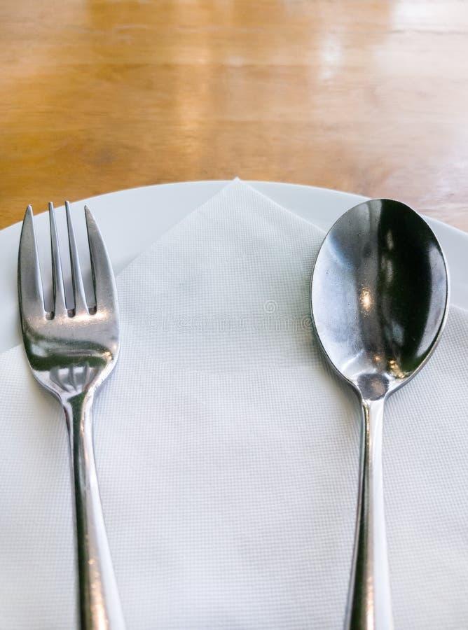 Белая плита с серебряной ложкой и вилкой стоковые изображения rf