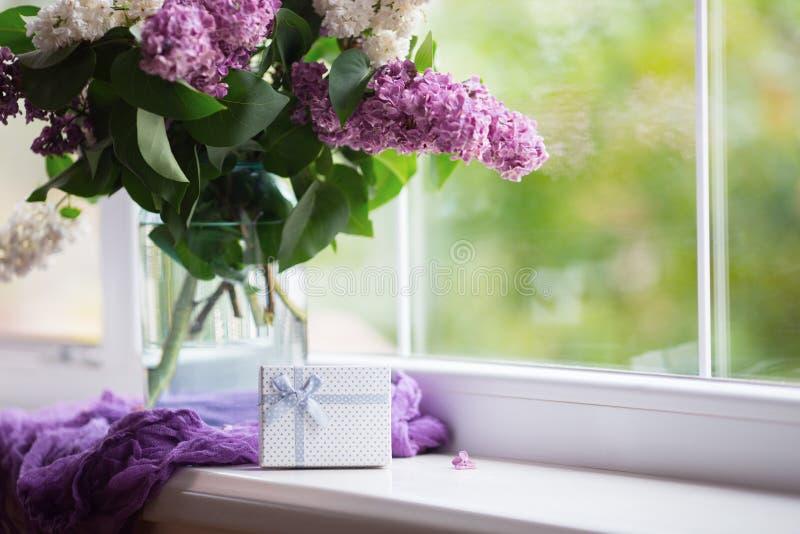 Белая подарочная коробка и нежный букет красивой сирени в стеклянной вазе около окна в дневном свете стоковое изображение