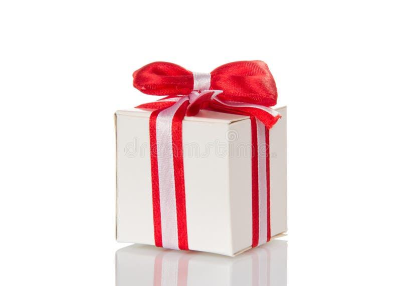 Белая подарочная коробка при striped лента и красный смычок изолированные на whi стоковое фото